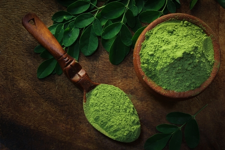 Photo pour Overhead view of Moringa powder in an earthern pot on dark wooden background - image libre de droit