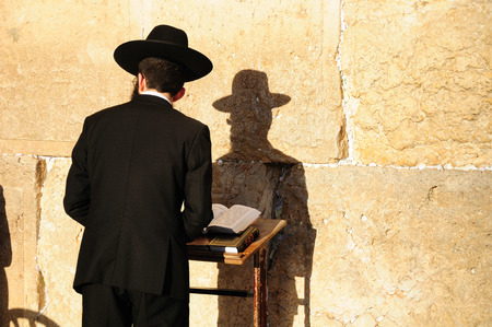 Religious orthodox jew praying at the Western wall in Jerusalem old city.