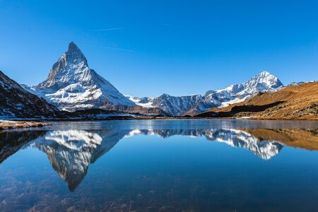 Photo for Stunning panorama view of the famous Matterhorn and Weisshorn peak of Swiss Pennine Alps with beautiful reflection in Riffelsee lake on sunny autumn near train station Riffelberg, Valais, Switzerland - Royalty Free Image