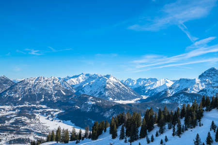 Photo pour Panorama view of  snow covered Austrian Alps in winter above the small town Reutte, with ski slope and skiing people in foreground, Tyrol, Austria - image libre de droit