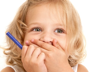 Laughing little girl covers her mouth with her hands and holding a pencil in her hand close-up on  white background