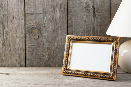 Foto de Empty brass picture frame and table lamp on old wooden gray textured background. Home decor and copy space for text. - Imagen libre de derechos