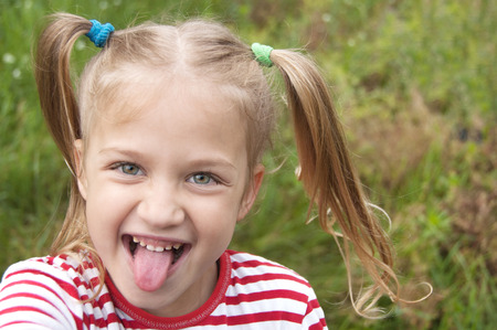 Photo pour Ð¡heerful cute blonde girl with ponytails shows tongue close up on the background of green grass. Copy space for text. - image libre de droit