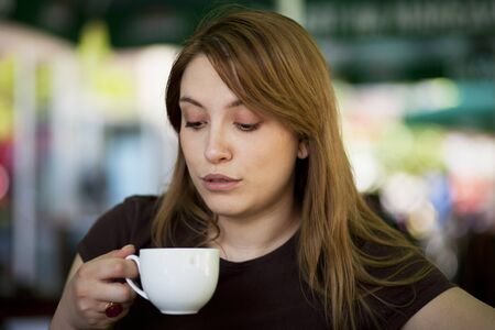 Photo for Young woman drinking hot beverage in a restaurant - Royalty Free Image