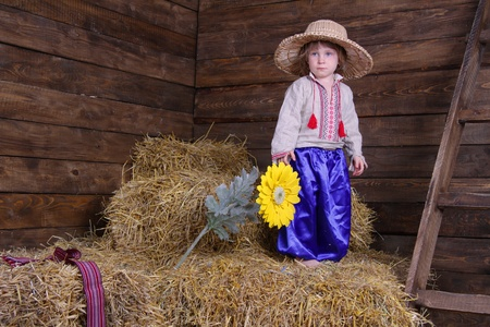 cute child in traditional eastern european clothes on hayloft