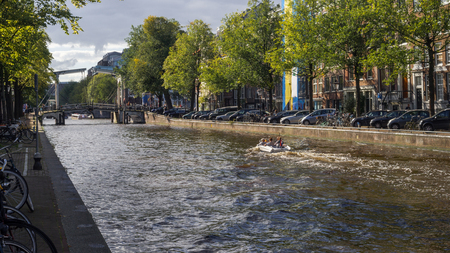 View on Boat, Bridgeand Traditional Architecture at Nieuwe Herengracht Canal in Amsterdam North Holland, The Netherlands.