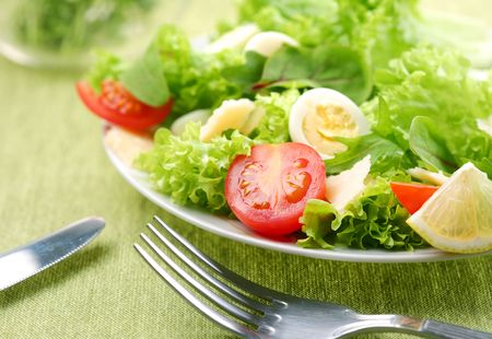 Fresh salad with tomato and quail eggs in a white bowl on a green tablecloth