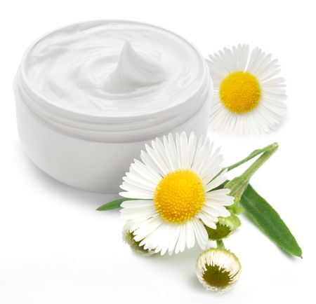 Photo pour Opened plastic container with cream and camomile on a white background. - image libre de droit