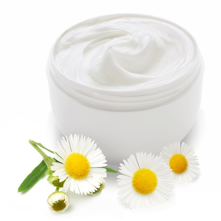 Opened plastic container with cream and camomile on a white background.