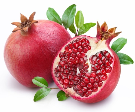 Juicy pomegranate and its half with leaves. Isolated on a white background.
