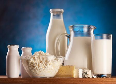 Different milk products: cottage cheese, cream, milk, yoghurt.  On a blue background.