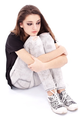 Sad girl teenager sits twining arms about legs. Isolated on a white background.