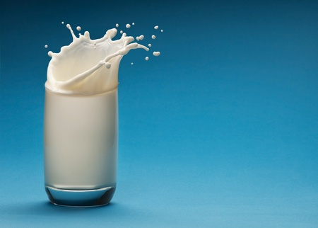 Splash of milk from the glass on a blue background