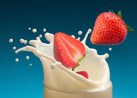 Splash of milk, caused by falling into a ripe strawberry. Isolated on a blue background.