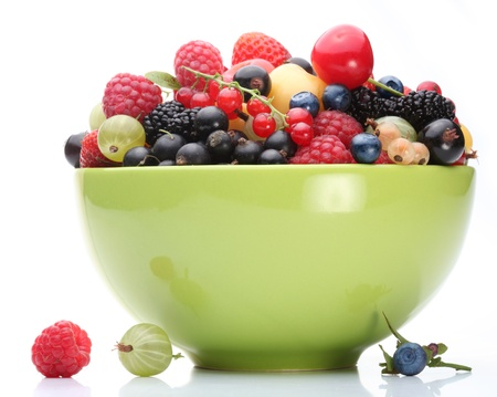 Variety of berries in a green bowl on white background.