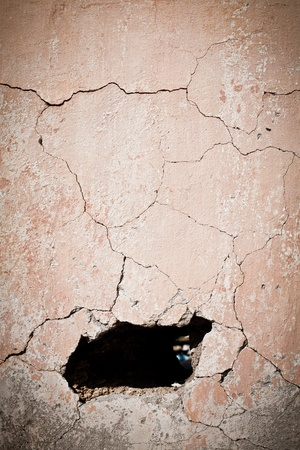 Hole in old cracked wall