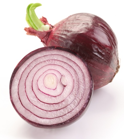 Bulbs of red onion with green leaves on a white background.