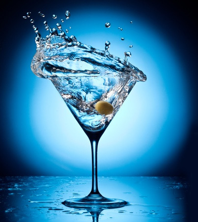 Photo pour Splash martini from flying olives  Object on a blue background  - image libre de droit