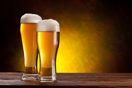 Photo pour Two glasses of beers on a wooden table  Dark yellow background  - image libre de droit