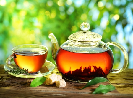 Photo pour Cup of tea and teapot on a blurred background of nature  - image libre de droit