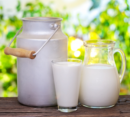 Milk in various dishes on the old wooden table in an outdoor setting