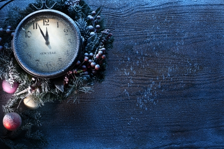 Christmas clock over snow wooden background. Five to twelve.の写真素材