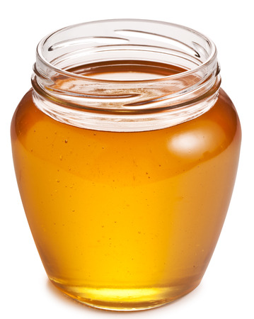 Opened glass can full of honey.の写真素材
