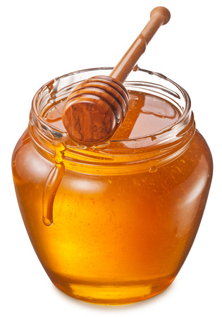 Glass can full of honey and wooden stick in it. Clipping paths.の写真素材