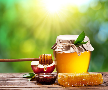 Glass can full of honey, apple and combs on wooden table at the nature background.の写真素材