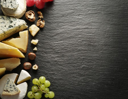 Different types of cheeses with wine glass and fruits. Top view.の写真素材