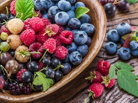 Photo pour Ripe berries in the wooden bowl on the table. - image libre de droit