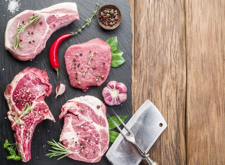 Raw meat steaks with spices on the wooden cutting board.