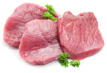 Raw beaf steaks with parsley on a white background.