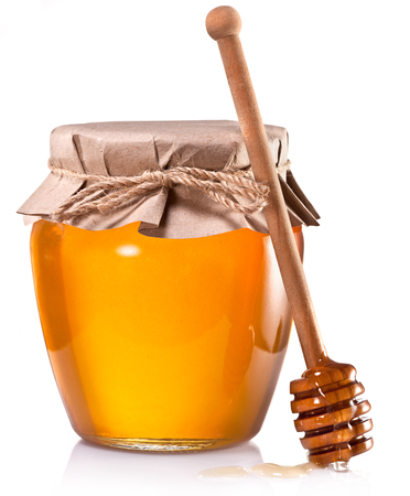 Glass can full of honey and wooden stick on a white background.の写真素材