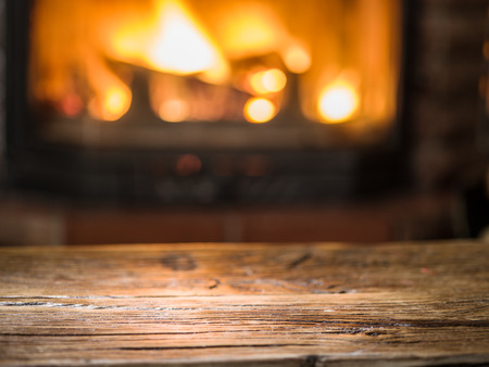 Foto de Old wooden table and fireplace with warm fire on the background. - Imagen libre de derechos