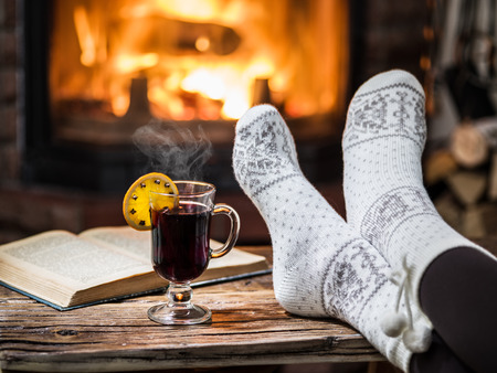 Warming and relaxing near fireplace. Woman feet near the cup of hot wine in front of fire.