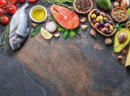 Photo for Raw dorado fish and salmon steak with spices and vegetables on the graphite board. Top view. - Royalty Free Image