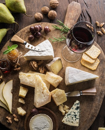Photo for Cheese platter with organic cheeses, fruits, nuts and wine on wooden background. Top view. Tasty cheese starter. - Royalty Free Image