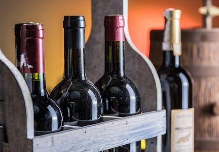 Foto de Wine bottles in wooden crate and oak wine keg. - Imagen libre de derechos