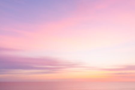 Defocused sunset sky and ocean nature background with blurred panning motion.