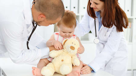 Photo pour Happy smiling girl-child at usual medical inspection. Doctor and female toddler patient in the clinic. Medicine, healthcare concepts - image libre de droit