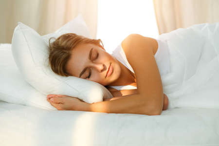 Photo for Beautiful blonde girl sleeping sweetly in sunny bedroom on a white bed. Holyday comfort and Rest concepts - Royalty Free Image