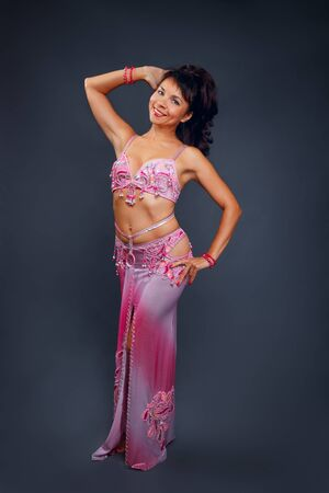 Photo pour Belly dancer performing belly dance in the ethnic pink costume for dancing on gray background - image libre de droit