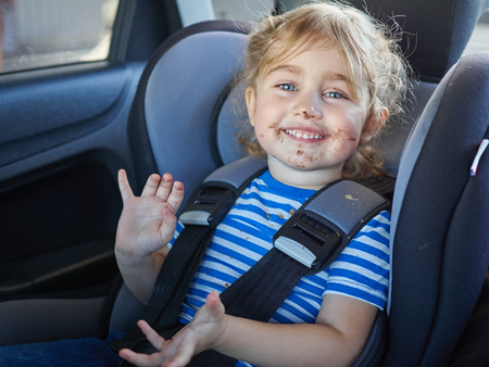 Photo pour Little dirty girl , baby in a safety car seat. Safety and security - image libre de droit