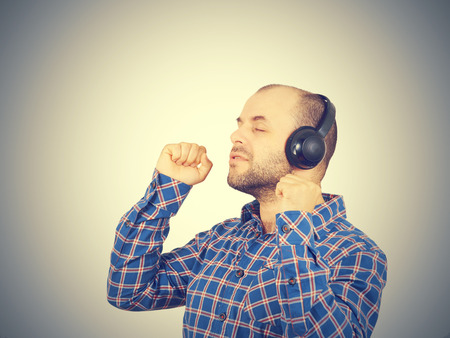 Men in headphones listens to music and sings. Isolated on a gray background.