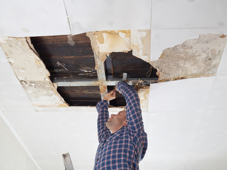 Photo pour Man repairing collapsed ceiling. Ceiling panels damaged  huge hole in roof from rainwater leakage.Water damaged ceiling . - image libre de droit