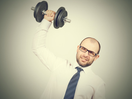 Man Trained businessman raises dumbbell. Isolated on  gray background