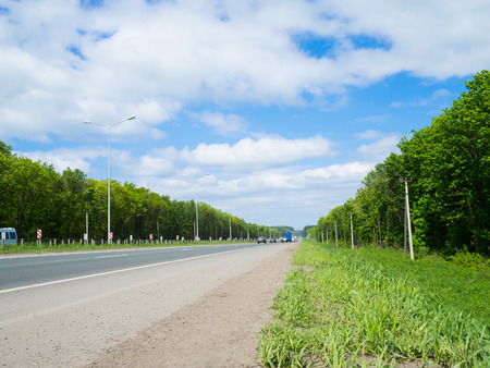 road with moving cars and green surroundings on the sides. highway receding into the distance beyond the horizon.