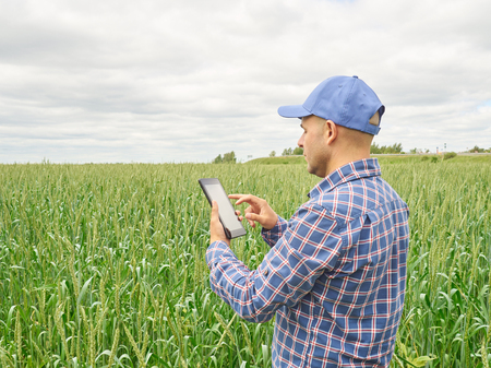 Foto de Farmer in a plaid shirt controlled his field and looking at tablet - Imagen libre de derechos