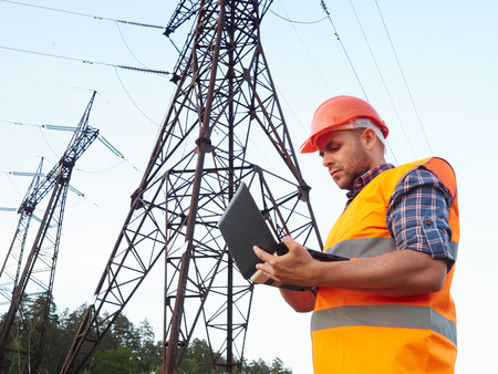 Photo pour Electrical engineer working. Talking on the phone and working working on a laptop.Checking the power grids. - image libre de droit